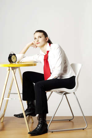 dullness: Woman sitting and waiting beside an alarm clock. LANG_EVOIMAGES