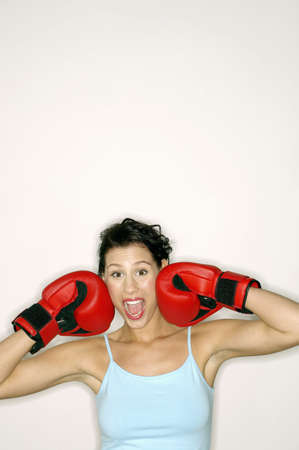 Woman with boxing gloves boxing her own face. Stock Photo - 3192559