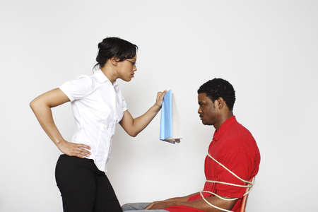 Woman forcing a tied up man to study.