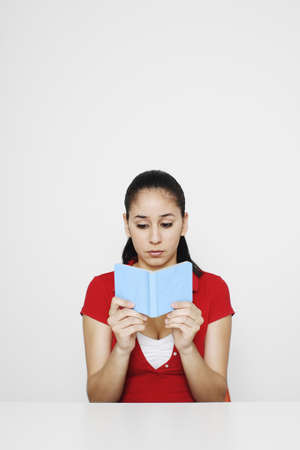 revision book: Woman reading a small book.