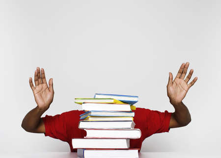exam preparation: Man with a stack of revision books.