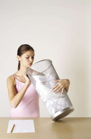 Girl looking into a dustbin of crumpled papers. Stock Photo - 3192572