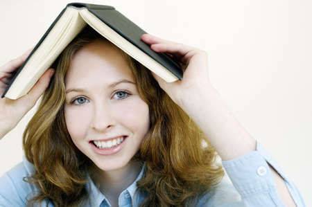 revision book: Woman covering her head with a book. LANG_EVOIMAGES