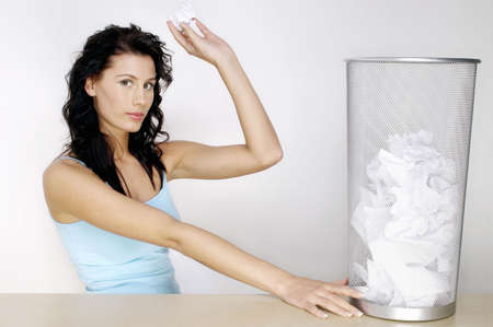 Woman about to throw a crumpled paper into the dustbin. Stock Photo - 3192575