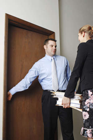 gratified: Businessman helping his colleague to open the door.