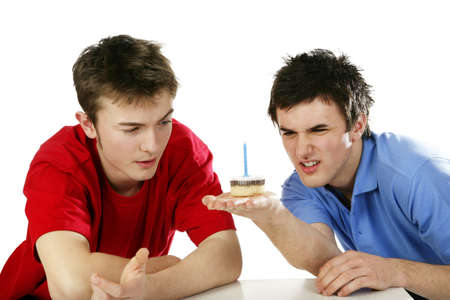 Men looking at a small birthday cake.