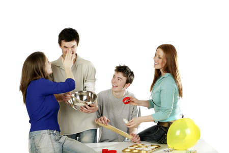 Men and women having fun baking cake together.