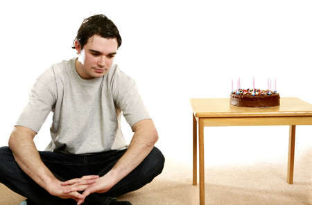 Man sitting beside his birthday cake. LANG_EVOIMAGES