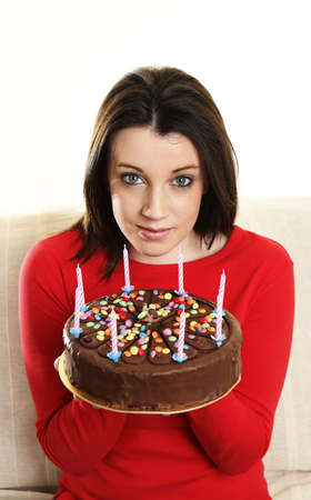 Woman holding a birthday cake. LANG_EVOIMAGES