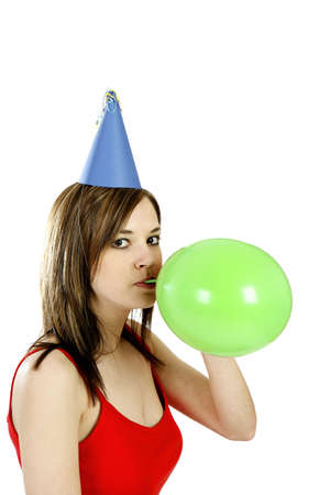 Woman with party hat blowing a balloon.