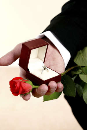Hand holding a wedding ring and a rose for proposal.