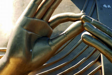 Close-up on the fingers of a golden statue.