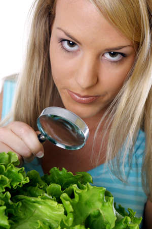 Woman viewing vegetables with a magnifying glass. Stock Photo - 3191171