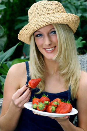 Woman holding a plate of strawberries.