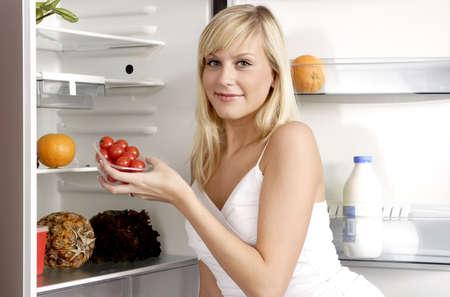 alimentacion equilibrada: Mujer sacar una caja de tomates de la nevera.