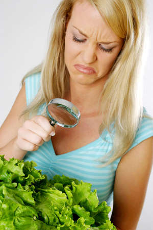 disgusted: Woman viewing vegetables with a magnifying glass.