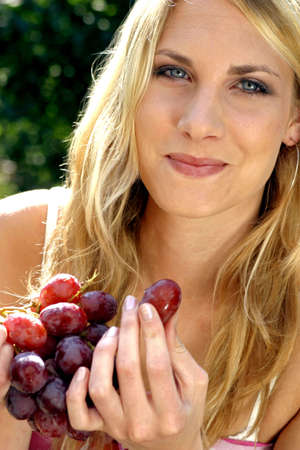 Woman holding grapes.