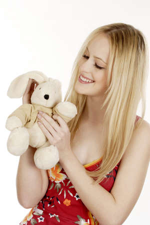 expressive mood: Woman playing with her bunny soft toy. LANG_EVOIMAGES
