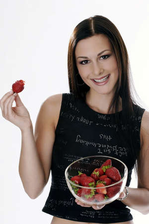 Woman holding a bowl of strawberries.