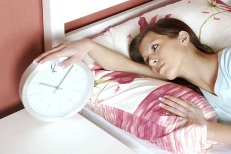 slack: Woman checking the time on the alarm clock. LANG_EVOIMAGES