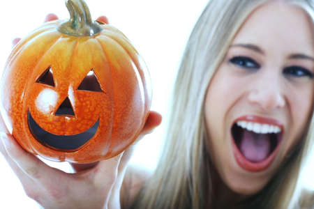 Woman holding a carved pumpkin.