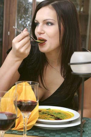 consuming: Woman enjoying a bowl of soup.