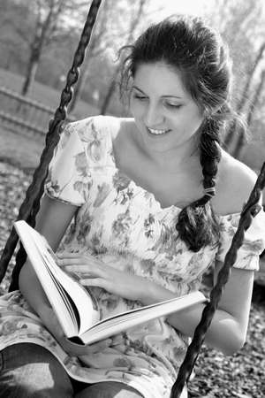 Woman reading book while sitting on the swing. LANG_EVOIMAGES