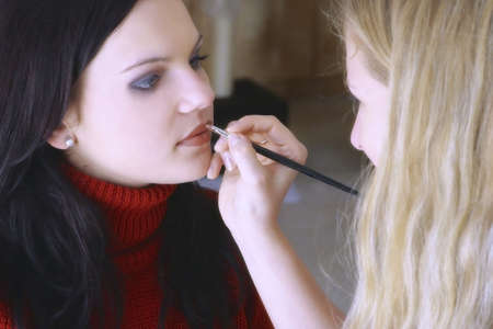 pouty: Woman applying colour on her friends lips.
