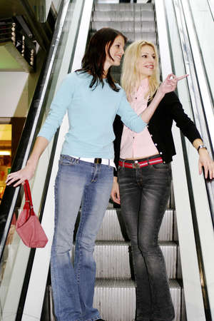Two women standing on the escalator. LANG_EVOIMAGES