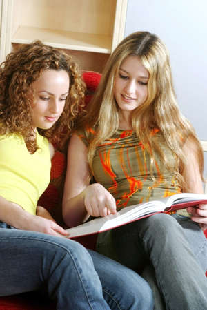 revision book: Two women sharing a book.