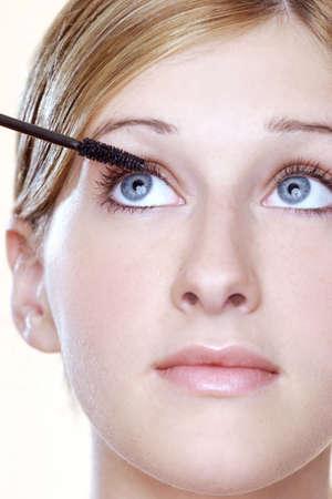 Woman applying mascara.
