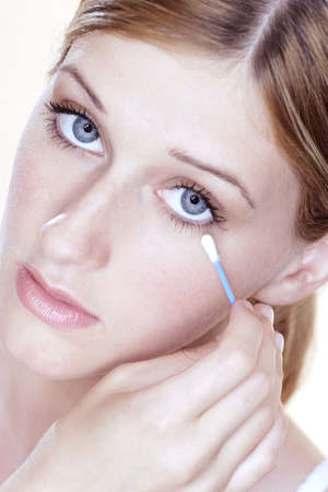 undereye: Woman cleaning her undereye with a cotton bud.