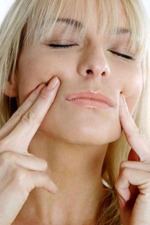 Woman massaging her face.