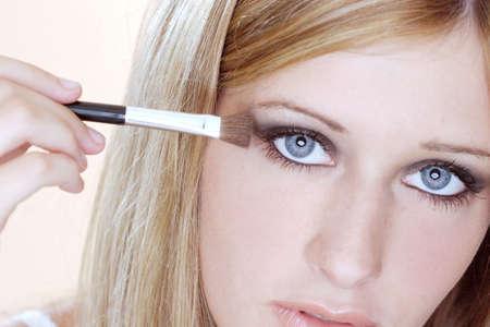 Woman applying eye shadow.