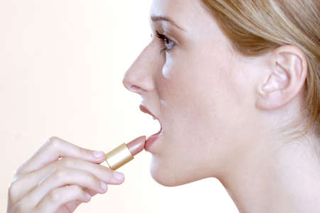 Woman applying lipstick. Stock Photo - 3191438