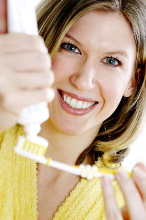 Woman squeezing some toothpaste on her toothbrush. Stock Photo - 3191454