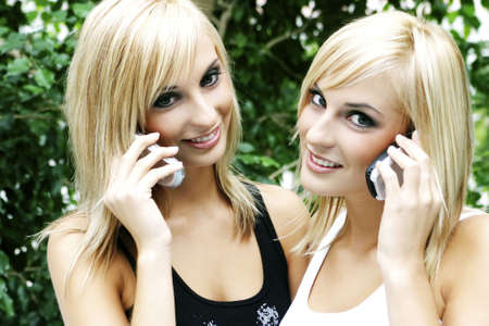Twin sisters talking on their mobile phones. LANG_EVOIMAGES