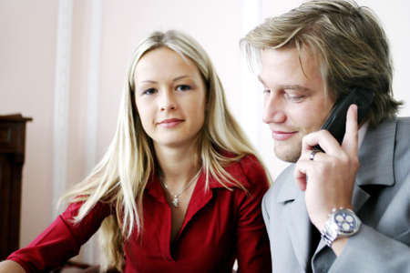 Businessman talking on the mobile phone with his secretary sitting by the side. Stock Photo - 3191557