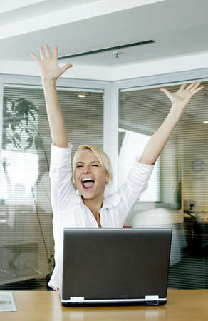 Businesswoman rejoicing after reading the good news in her e-mail.