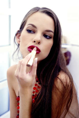 Woman puckering her lips while applying lipstick