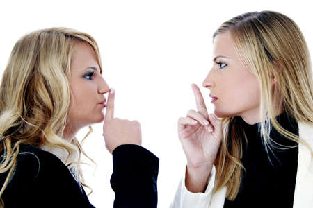 hushing: Two businesswomen showing hushing sign while looking at each other LANG_EVOIMAGES
