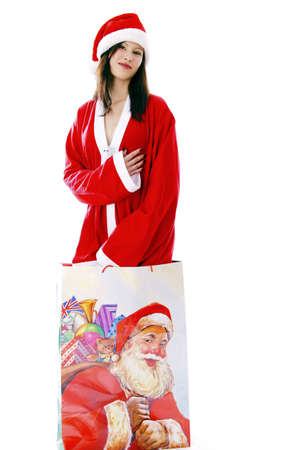 Sexy woman in santa suit, standing in a big shopping bag