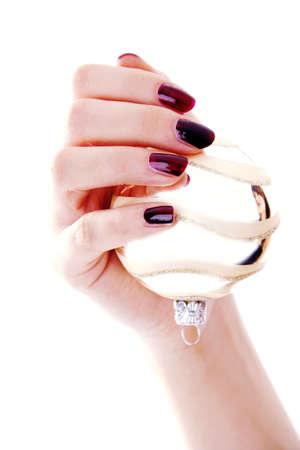 christmas manicure: Hand holding a Christmas ball ornament