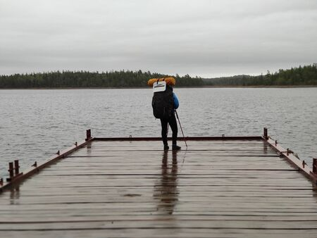 Girl tourist stands on a pier of the big lake