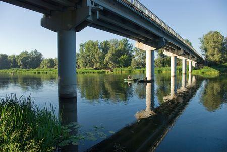 Fishing under the bridge. Stock Photo