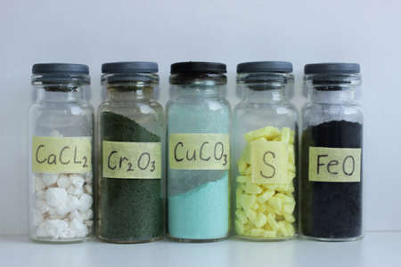 Various inorganic substances in glass jars: white large crystals of calcium chloride, green chromium oxide, blue copper carbonate, yellow sulfur crystals, black iron oxide powder.