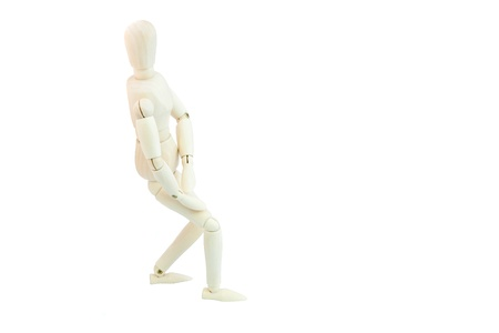 Articulated Wooden Dummy pushing a wall isolated on white background Stock Photo