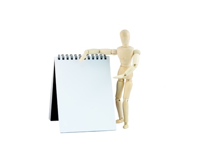 articulated wooden dummy indicating something in a notebook on white background Stock Photo