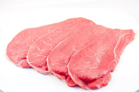 several steaks isolated on white background