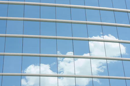 blue glass wall of office building with sky reflect